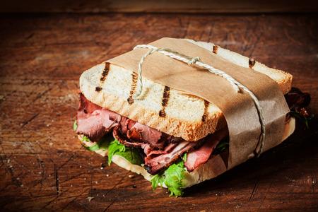 carne asada: Delicioso sándwich de carne asada rara en pan tostado a la parrilla envuelto en papel marrón atado con una cuerda que se presentan en un mostrador de madera en un restaurante rústico