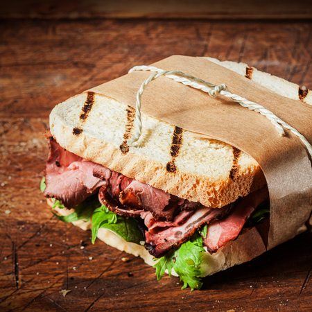 Grilled roast beef ,spinach and rocket sandwich tied in a brown paper takeaway wrapper on an old wooden rustic table,close up view photo