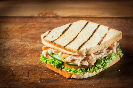 Healthy toasted chicken breast sandwich with shredded meat on fresh salad ingredients including lettuce, tomato and cucumber, on a rustic wooden table with copyspace and vignetting photo