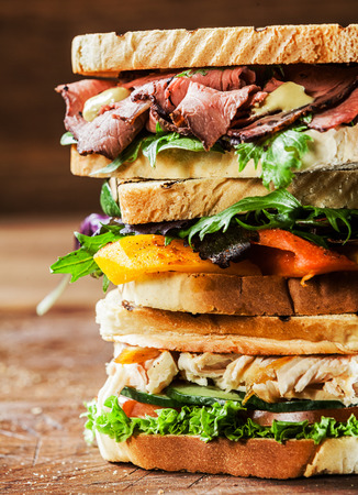 Stack of three delicious toasted sandwiches with different fillings including rare roast beef,shredded chicken breast and pepper and cheese all garnished with herb and salad ingredients,close up view photo