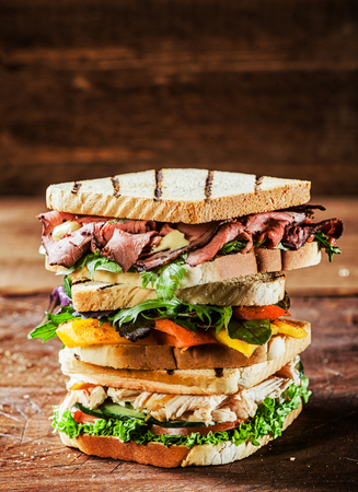 Choice of tasty toasted sandwiches piled on top of each other with shredded chicken breast, rare roast beef and cheese garnished with pepper, herbs and salad ingredients on a rustic table , copyspace photo