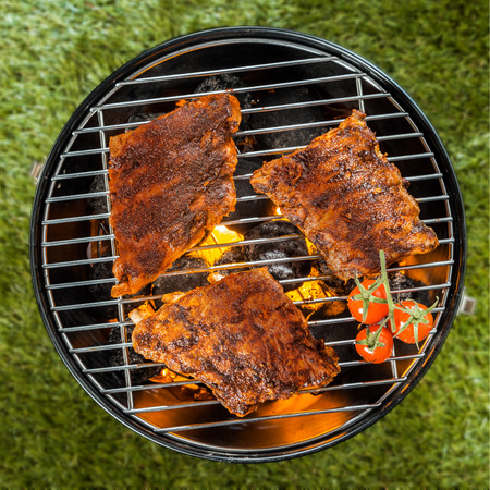 View from above of three delicious seasoned racks of rib grilling over a BBQ fire in a portable round metal barbecue on green grass
