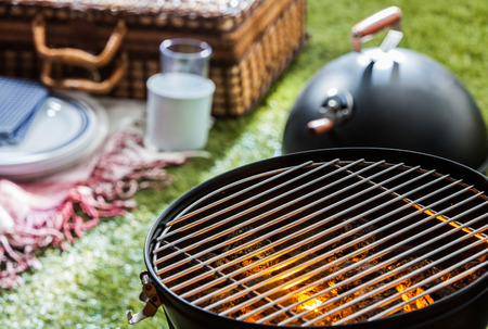 charcoal grill: Close up of a burning hot fire in a portable barbecue with an empty grill and a wicker picnic hamper visible on a green lawn behind