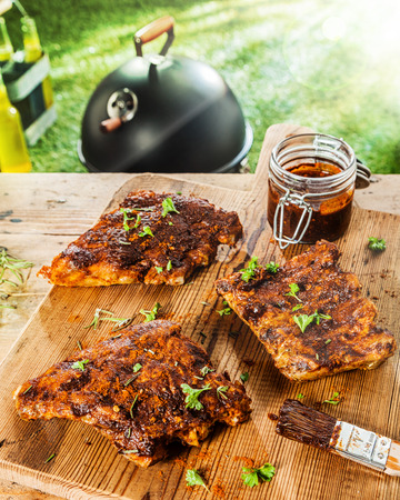 marinate: Preparing ribs for a BBQ with savory basting sauce and finely chopped fresh herbs with three portions on a table with a jar of marinade and a brush