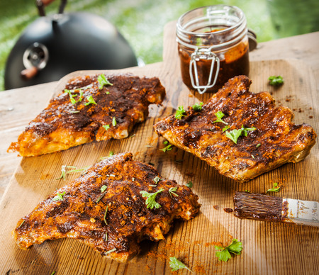 Seasoned ribs on a rustic wooden picnic table at a BBQ in the garden with fresh herbs and a glass jar of spicy marinade or basting sauce photo