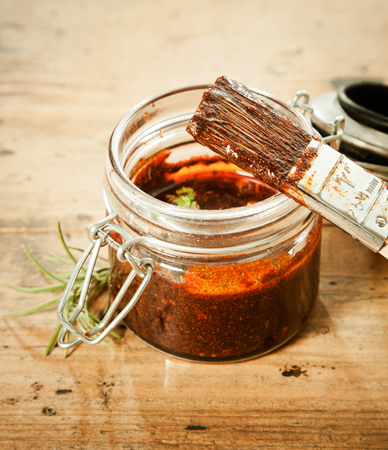 marinade: Savoury BBQ basting sauce in a glass jar with a basting brush and sprig of fresh rosemary for seasoning and flavoring the meat