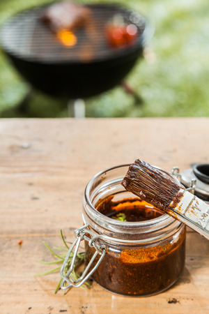 marinate: Jar of basting sauce and a basting brush standing on a wooden picnic table outdoors for the meat grilling on the BBQ in the background on a green lawn