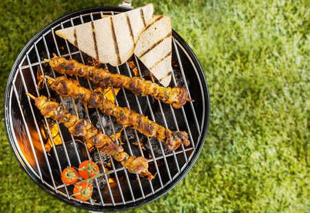 non vegetarian: View from above of two lamb, beef or pork kebabs with slices of toast and tomatoes grilling on a BBQ fire on a portable metal barbecue during a summer picnic on green grass with copyspace