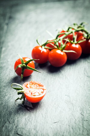lycopene: Grape tomatoes on the vine with a single halved tomato in the foreground on a textured surface with highlight and copyspace and shallow dof