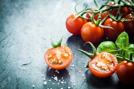 Frische Trauben Tomaten mit Basilikum und grobem Salz für die Verwendung als Kochzutaten mit einer halbierten Tomate in den Vordergrund mit Exemplar