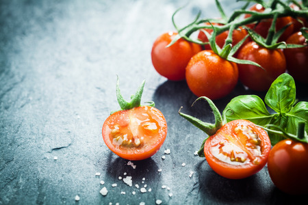 Fresh grape tomatoes with basil and coarse salt for use as cooking ingredients with a halved tomato in the foreground with copyspace Stockfoto