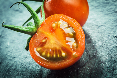 pips: Close up of a halved juicy fresh grape tomato showing the pips and pulp with a green stalk for a healthy salad or cooking ingredient