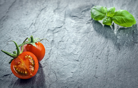 dark cherry: Fresh halved tomato and fresh basil arranged in the the opposite corners of the frame on a dark textured surface at a low angle perspective with copyspace