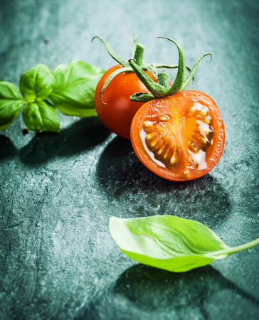 Fresh basil leaves with halved juicy ripe red grape tomatoes ready for cooking a savory dish on a dark textured surface photo