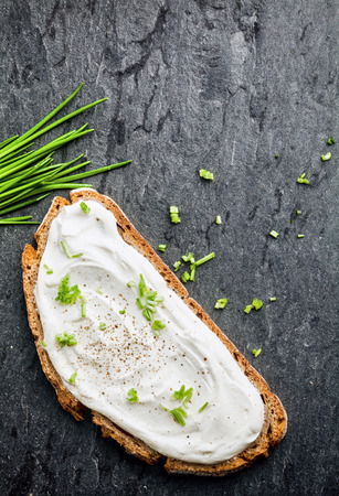 quark: Overhead view of delicious cream cheese and chopped chives on a slice of rye or wholewheat bread on a dark textured surface with copyspace Stock Photo