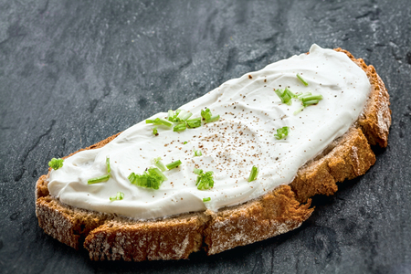 quark: Healthy low fat cream cheese and chopped chives on a slice of freshly baked rye bread, close up low angle view Stock Photo