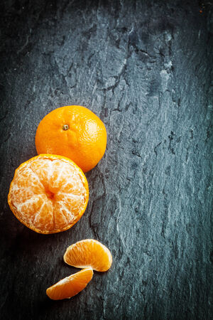 dark grey slate: Peeled fresh clementine or tangerine with segments and a whole fruit arranged in a corner on a dark slate background with texture, copyspace and vignetting