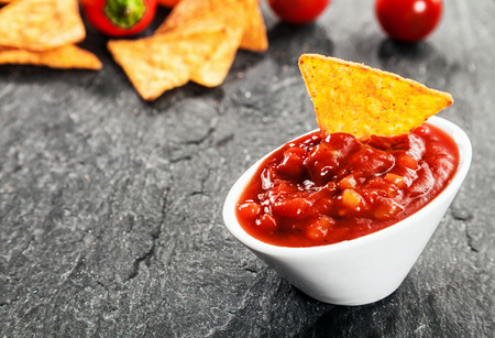 dark grey slate: Serving of hot spicy salsa sauce made with tomato and chili peppers in a bowl with corn tortillas or nachos to dip for a savory appetizer Stock Photo