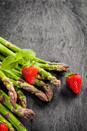 dark grey slate: Fresh uncooked green asparagus spears, strawberries and peppermint on a grey textured slate surface with copyspace in vertical format