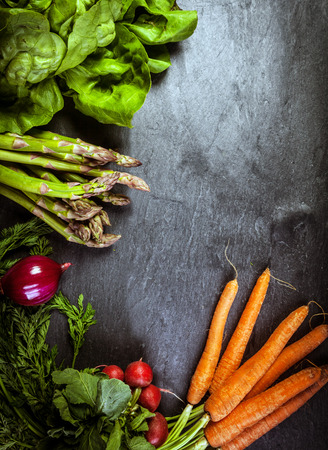 dark grey slate: Fresh vegetable frame or border on textured slate with copyspace for your text with farm fresh bunches of asparagus spears, carrots, radish spinach and beetroot Stock Photo