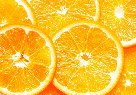 pith: Background texture of fresh juicy ripe overlapping orange slices showing the structure and pattern of the pith and segments