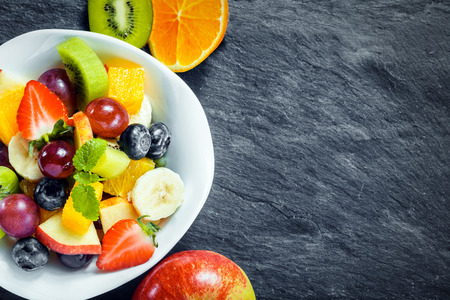 fruity salad: Overhead view of a bowl of fresh fruit salad for a healthy diet made with assorted tropical fruits and an apple, kiwifruit and orange arranged alongside on textured slate with copyspace Stock Photo