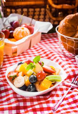 Healthy vegetarian summer picnic with a box of assorted whole fresh fruit and bowl of colourful tropical fruit salad with a hamper on a red and white checked tablecloth photo