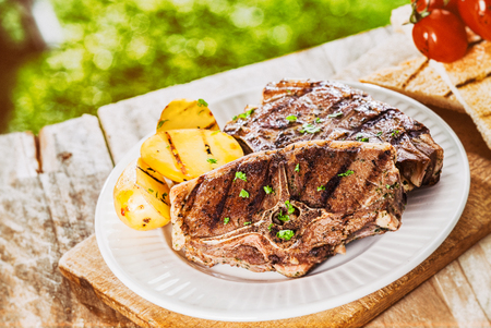 Serving of grilled lamb chops garnished with chopped fresh herbs and potato at a BBQ on a rustic wooden picnic table in the garden photo