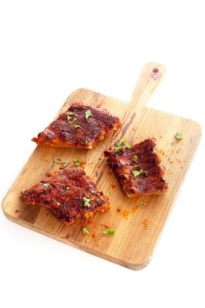 costilla: Las porciones de costillas a la barbacoa picantes sazonados con condimentos aromáticos y hierbas frescas en una tabla de cortar de madera, aislado en blanco Foto de archivo
