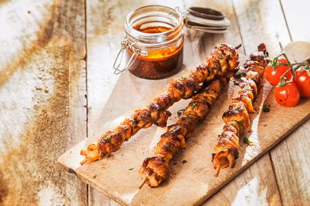 pinchos morunos: Picantes kebabs de carne a la parrilla en un picnic de verano que se presentan en una tabla de cortar de madera con tomates asados ??junto a un frasco de salsa de asar picante, con copyspace