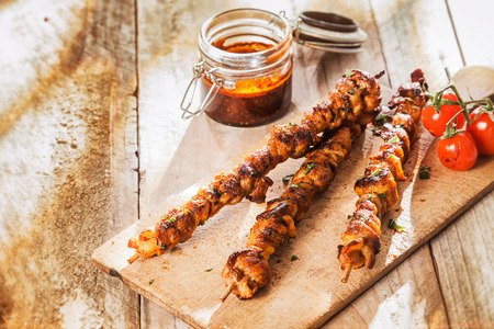 marinate: Spicy grilled meat kebabs on a summer picnic served on a wooden chopping board with roast tomatoes alongside a jar of piquant basting sauce, with copyspace