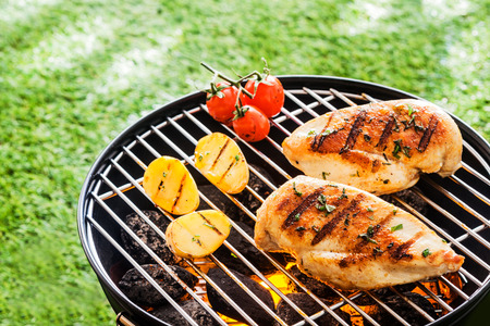 Lean healthy chicken breasts grilling over the hot coals on a portable BBQ with fresh tomatoes and potatoes for a healthy low fat meal