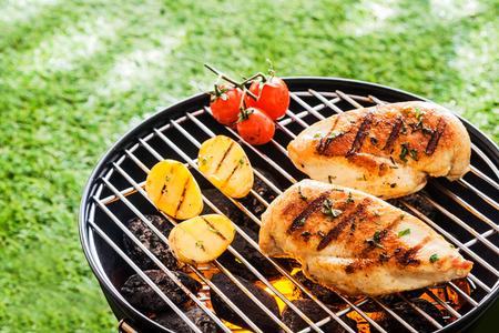 Lean poitrines de poulet en bonne santé griller sur les braises chaudes sur un barbecue portable avec des tomates fraîches et pommes de terre pour un faible repas sain de graisse