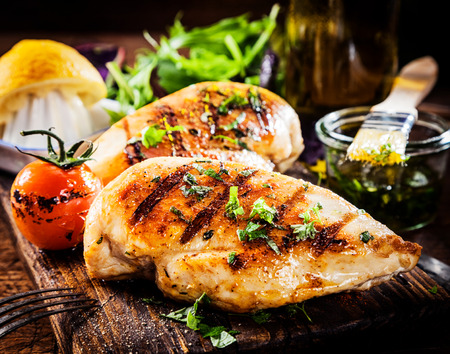 Marinated grilled healthy chicken cooked on a summer BBQ and served with fresh herbs and lemon juice on a wooden board, close up view