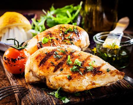 Marinierte gegrillte gesunde Hähnchenbrust gekocht auf einem Sommergrill und serviert mit frischen Kräutern und Zitronensaft auf einem Holzbrett, Nahaufnahme