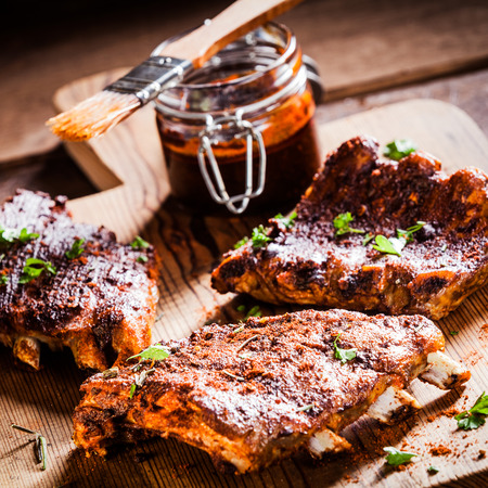 Three portions of barbecued ribs in a spicy marinade seasoned with pepper and fresh herbs being prepared in a country kitchen with a jar of basting sauce
