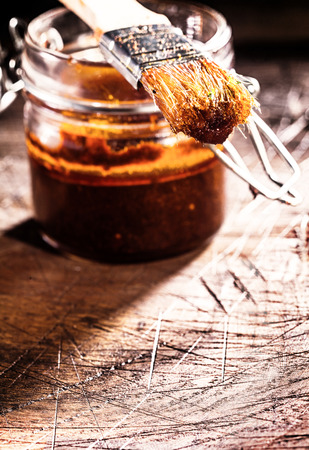 gouged: Glass jar of homemade spicy basting sauce and a brush on an old scored wooden chopping board in a rustic kitchen