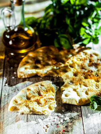 ovenbaked: Eating Italian focaccia bread, a high gluten ovenbaked flatbread flavored with olive oil and herbs, served on a rustic wooden table Stock Photo
