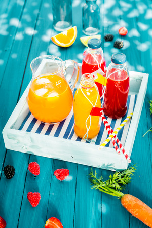 Bottles of freshly squeezed homemade citrus and berry juice with a jug of iced carrot and orange juice blend served on a wooden tray on a colorful turquoise picnic table outdoors photo