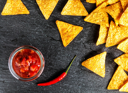 mexican black: Crisp golden corn totillas with hot salsa sauce and a red hot chili pepper for a spicy snack, overhead view on a slate surface Stock Photo