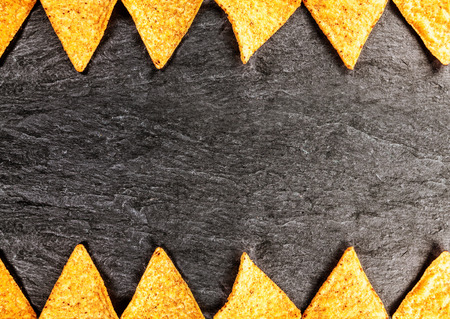 NACHO: Border of golden crisp nachos or corn tortillas arrange top and bottom in a geometric pattern in horizontal format on textured slate with copyspace