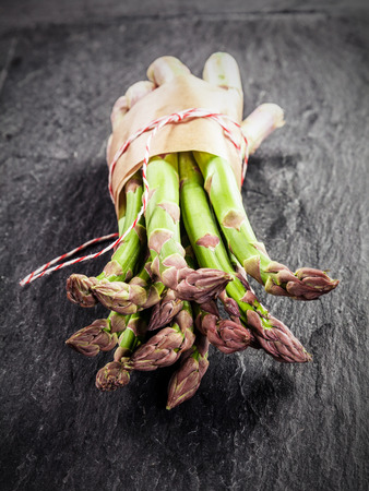 dark grey slate: Fresh green asparagus spears bundled in brown paper and tied with string displayed with their tips to the camera on a grey textured slate surface