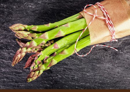 Fresh green asparagus shoots tied in a bundle with brown paper and string, close up overhead view on dark slate with copyspace