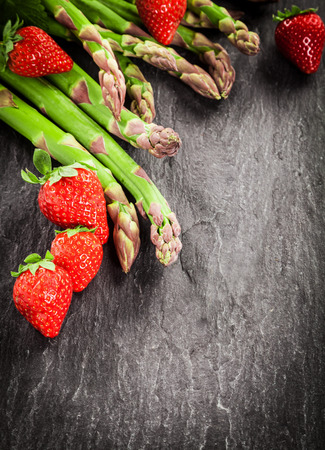 dark grey slate: Fresh uncooked green asparagus spears and ripe red strawberries arranged as a corner decoration on textured grey slate with copyspace and vignetting