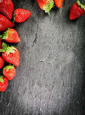 vignetting: Border of whole fresh ripe red strawberries arranged on two sides on a dark grey textured slate background with copyspace and vignetting