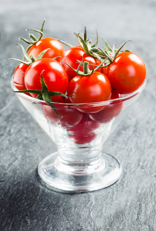 Fresh ripe red juicy cherry tomatoes with stalks served in a conical glass container as crudites to dip in a savory sauce photo