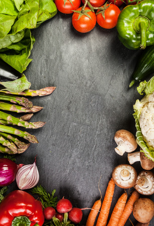 Frame or border of assorted farm fresh vegetables on slate with copyspace including carrots, asparagus, tomato, pepper, carrots , mushroom and radish Stok Fotoğraf