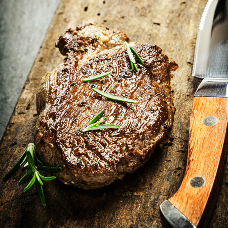 dark grey slate: Succulent portion of grilled beef steak garnished with fresh rosemary on a rustic wooden chopping board with a sharp steak knife for a gourmet meal