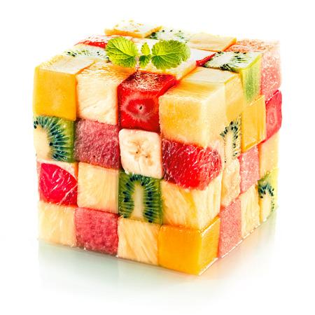 cube de fruits formé de petits carrés de fruits tropicaux assortis dans un arrangement coloré, y compris les kiwis, fraises, orange, banane et ananas sur un fond blanc