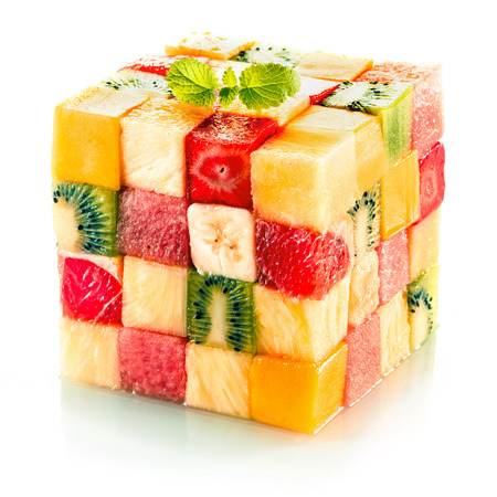 Fruit cube formed from small squares of assorted tropical fruit in a colorful arrangement including kiwifruit, strawberry, orange, banana and pineapple on a white background